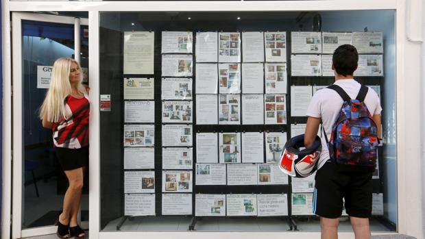 Un joven consulta los carteles de una agencia inmobiliaria