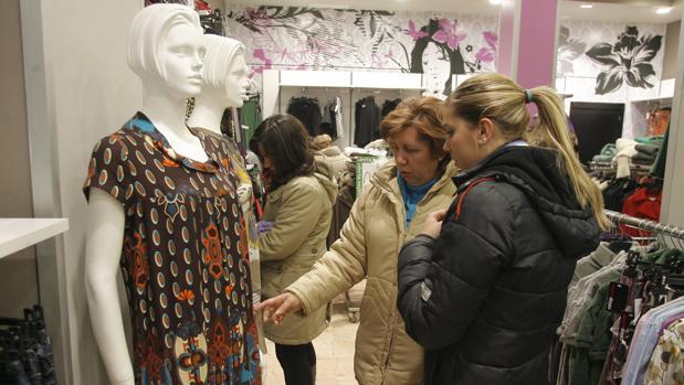 Dos clientas miran prendas de ropa en un negocio de moda