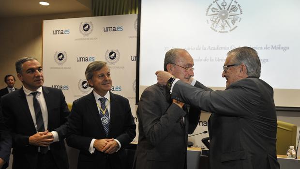 Antonio García del Valle impone al alcalde la medalla de honor junto al presidente de la Academia