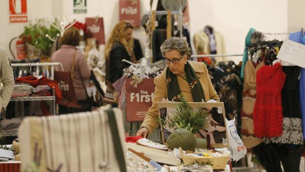 Una mujer observa uno de los puestos de esta nueva edición del Baratillo de Navidad de Adevida