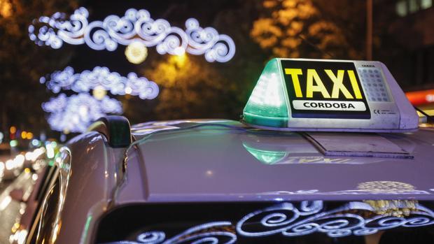 Un taxi circula por las calles de Córdoba bajo el alumbrado navideño
