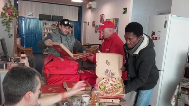 Personas sin hogar recibiendo las primeras pizzas