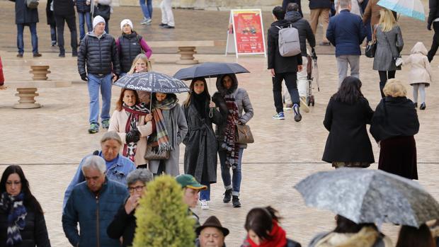 Turistas con paraguas en la zona de la Puerta del Puente de Córdoba