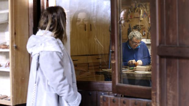 Una turista contempla las labores de un artesano del cuero en el Zoco municipal