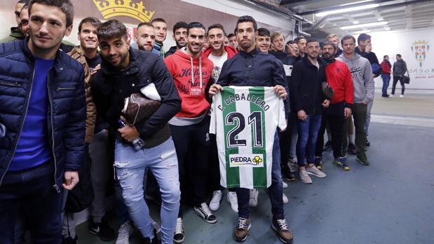 Carlos Caballero posa con toda la plantilla y su camiseta firmada