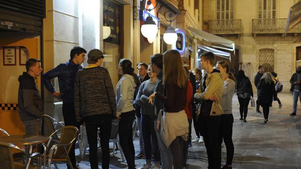 Jóvenes en la entrada de un bar de copas de la capital malagueña