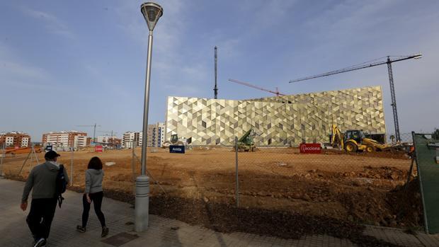 Dos personas pasan por delante del Hospital Quirón en obras