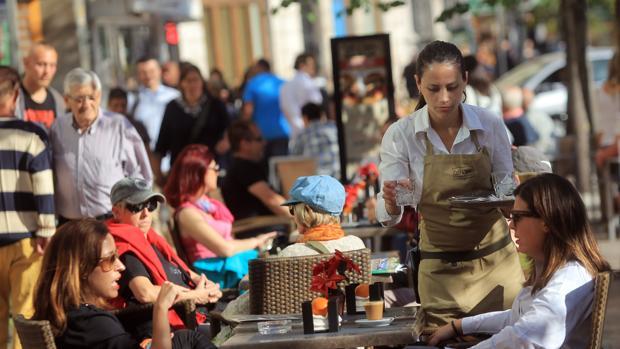 Una camarera sirve una mesa en la terraza de un bar