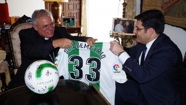 El presidente del Córdoba CF, Jesús León, entrega una camiseta al Obispo de Córdoba, Demetrio Fernández