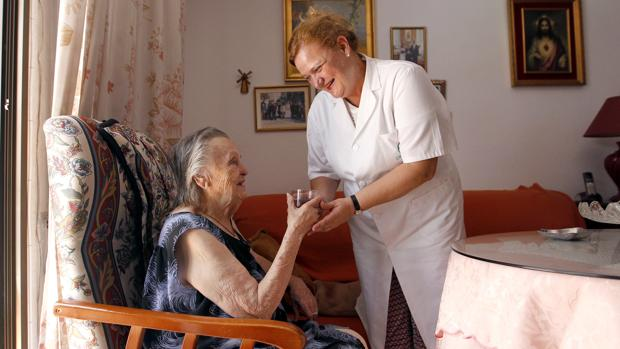 Una mujer de la ayuda a domiciñio en un hogar de Córdoba