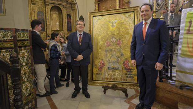 Juan Ignacio Reales, presidente de la Matriz y Raúl Berzosa, autor de la obra presentan el cartel de la Romería del Rocío 2018
