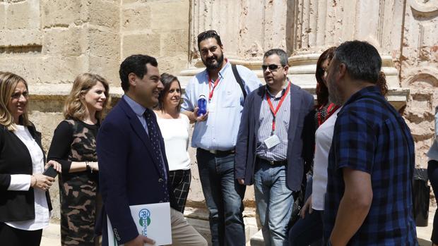 El presidente del PP andaluz, Juanma Moreno, charlando con los profesionales sanitarios en el Parlamento