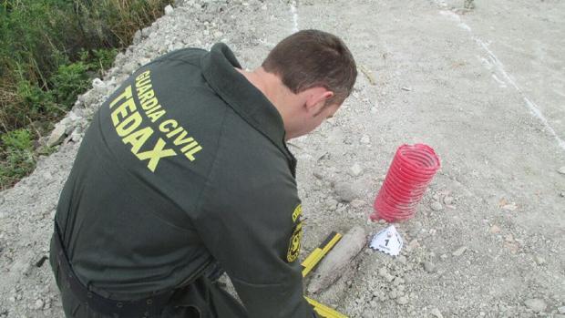 Un artificiero de la Guardia Civil mide el tamaño del proyectil