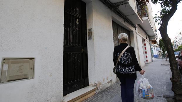 Una mujer pasa por delante del portal de la vivienda en la que sucedieron los hechos
