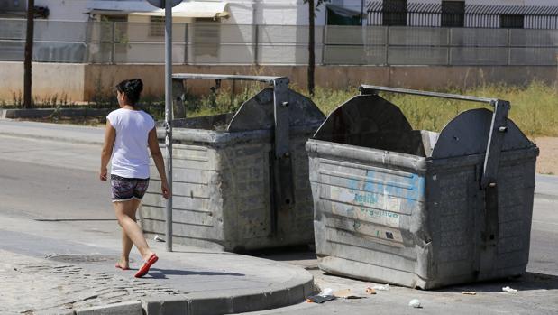 Una mujer pasa delante de dos contenedores quemados en la zona Sur de la ciudad