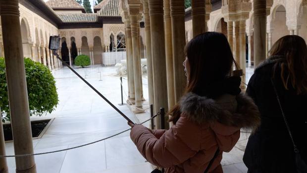 Una turista se hace una foto en el Patio de los Leones de la Alhambra, en Granada.