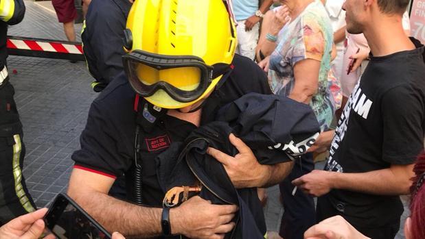 Un bombero con el águila rescatada envuelta en una chaqueta