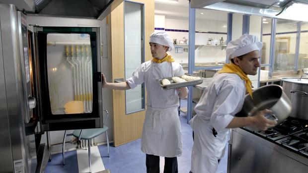 Dos jóvenes trabajan en las cocinas de la Escuela de Hostelería