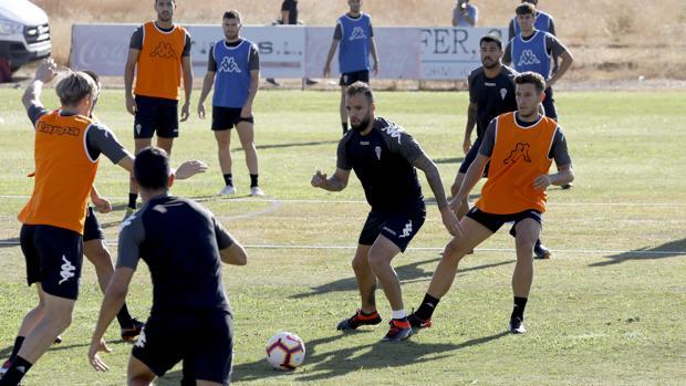 Víctor Mena, de naranja, defiende una acción durante un entrenamiento