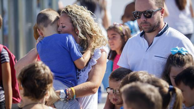 Concepción Sierra sostiene en brazos a su hijo a las puertas del colegio en el primer día de clase