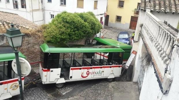El tren turístico de Granada, encajado tras derrapar en las calles del Albaicín.