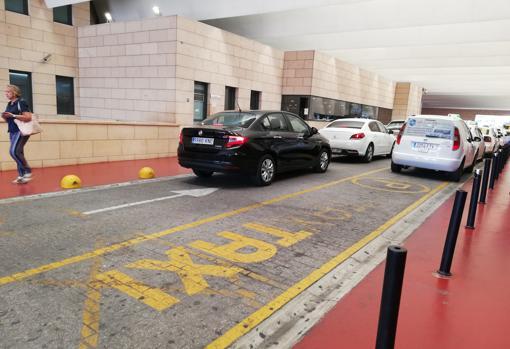 Un vehículo de Uber, a la izquierda, junto a los taxis de la parada del Reina Sofía