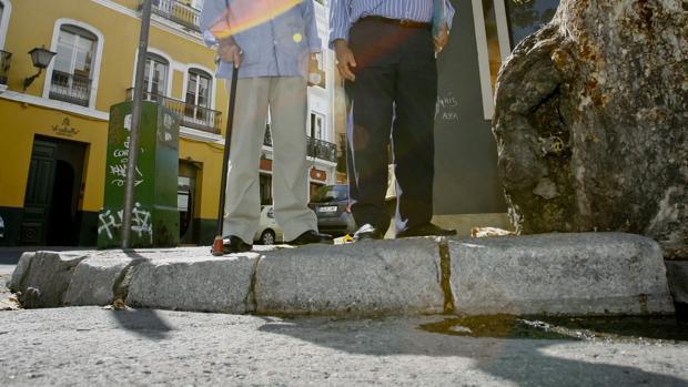 Dos personas mayores se detienen ante un bordillo no rebajado