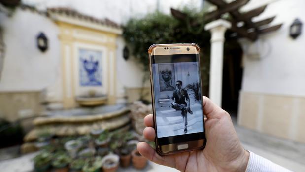 Una persona muestra la fotografía de Manolete en el mismo patio de la vivienda