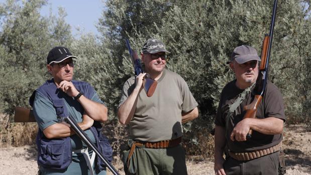 Tres cazadores durante una montería