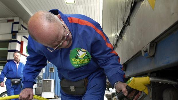 Un empleado llena el depósito de un camión de transporte de mercancias agrícolas