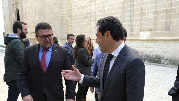 El presidente de la Junta, Juanma Moreno, tiende la mano a Francisco Serrano en el patio del Parlamento