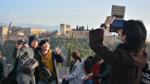 Turistas se fotografían frente a la Alhambra en el Mirador de San Nicolás.