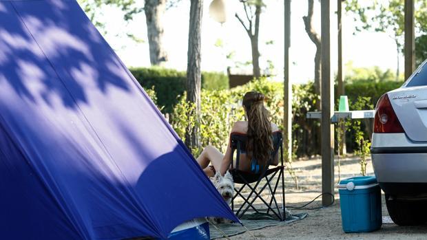 Una mujer junto a la tienda de campaña en un camping