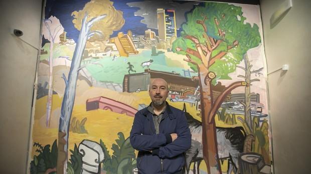 Manuel Garcés junto a su mural