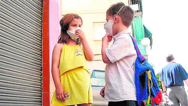 Dos niños con mascarilla camino del colegio