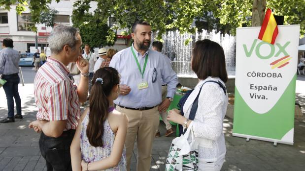 El candidato de Vox, Rafael Saco, habla con una familia en el Bulevar