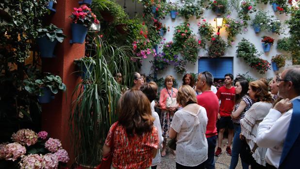 Visitantes de una ruta en el patio de la calle Martín de Roa, 2 oyen atentamente a su guía