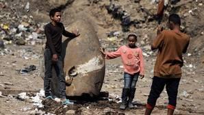 Dos niños posan junto a la cabeza recuperada de la estatua de Psamético
