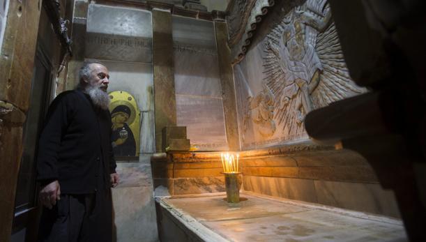 Un clero griego ortodoxo, fotografiado delante de la tumba de Jesucristo, en la Iglesia de la Santa Sepultura