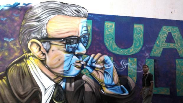 Un hombre pasa por delante de un mural con una imagen de Juan Rulfo en el municipio de Tuxcacuesco