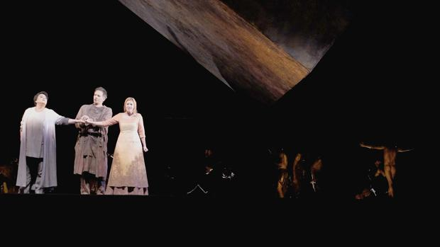 Tres de los cantantes de la ópera junto a la losa que domina la escenografía