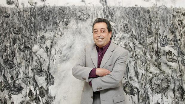 El pintor sevillano Paco Cuadrado posa delante de una de sus obras