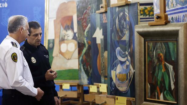Imagen de archivo. Un policía nacional y un policía autonómico conversan ante las obras falsas de Picasso que iban a venderse de forma ilícita en 2015