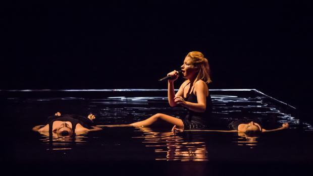 Joana Melo, rodeada de dos bailarines, cantando en el agua del montaje de Quorum Ballet