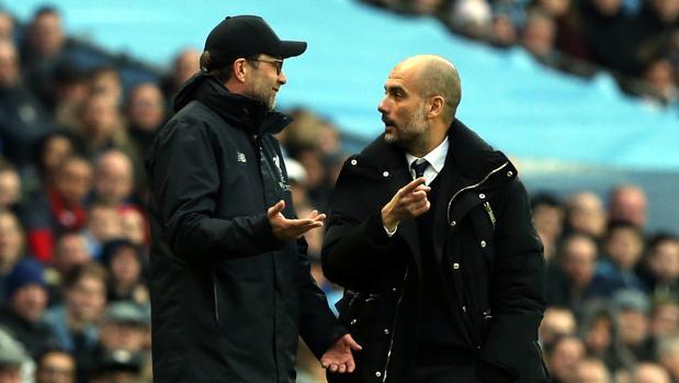 Klopp y Guardiola charlan en la banda del Etihad Stadium