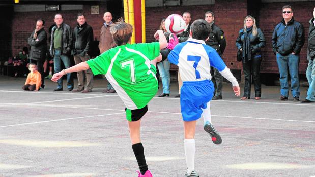 Unos niños juegan al fútbol en un torneo escolar ante la presencia de sus padres