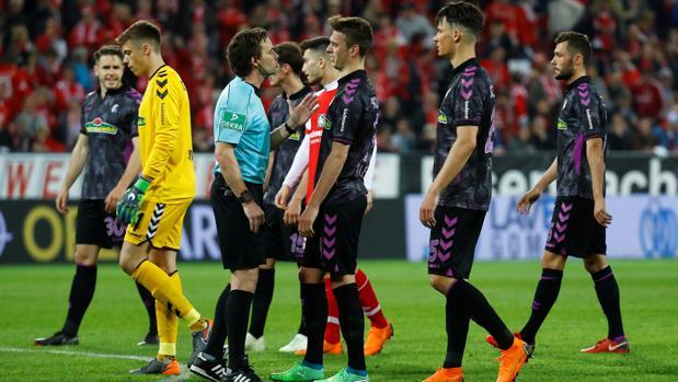 Jugadores del Friburgo hablan con el árbitro, Guido Winkmann
