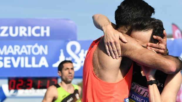 Dos participantes se abrazan tras cruzar la meta del Zurich Maratón Sevilla