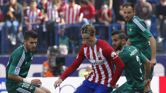 Torres, entre Ceballos, Montoya y Westermann, en una acción del Atlético-Betis (Foto: EFE)