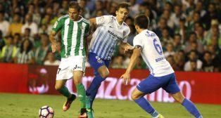 Joaquín trata de marcharse de dos jugadores del Málaga (Foto: J. M. Serrano)